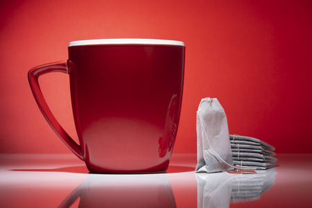 Red mug and a tea bags isolated on the red background