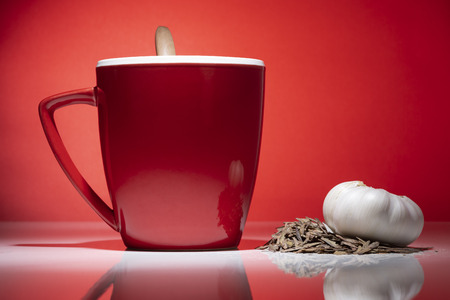 Red mug with small pile of tea, garlic and a wooden spoon isolated on the red background
