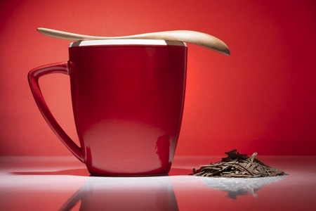 Red mug with small pile of tea and wooden spoon isolated on red background