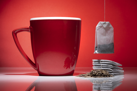 Red mug with small pile of tea and a tea bags isolated on the red background