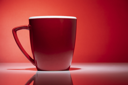 Red tea or coffee mug isolated on the red background 스톡 콘텐츠