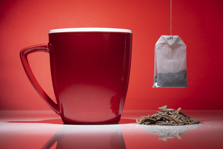 Red mug with small pile of tea and a tea bag isolated on the red background 스톡 콘텐츠