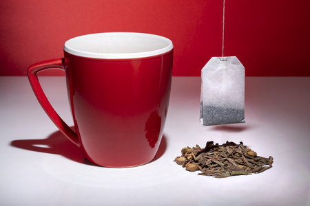 Red mug with small pile of tea and tea bag isolated on the red background 스톡 콘텐츠