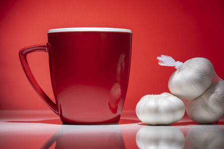 Red mug with small pile of garlic isolated on the red background