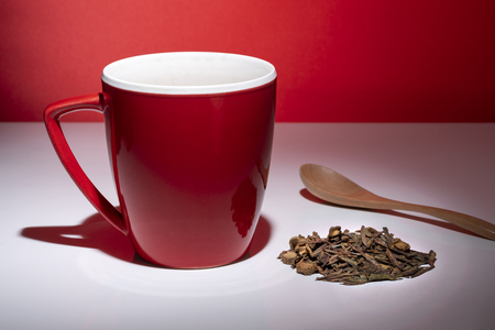 Red mug with small pile of tea and a spoon isolated on the red background 스톡 콘텐츠