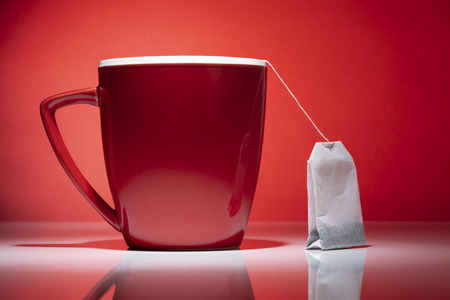 Red mug and a tea bag isolated on the red background