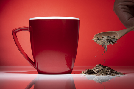 Red mug with small pile of tea and a wooden spoon isolated on the red background 스톡 콘텐츠