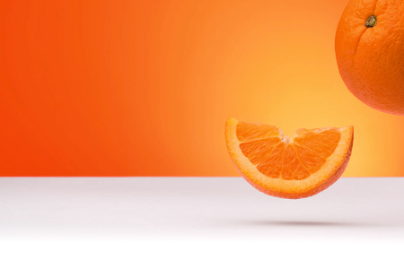 Floating oranges isolated on an orange and white background with space for text 版權商用圖片