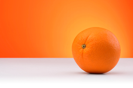 An orange isolated on an orange and white background with space for text