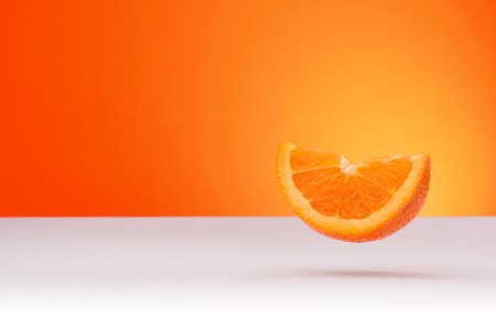 Floating piece of orange isolated on an orange and white background with space for text
