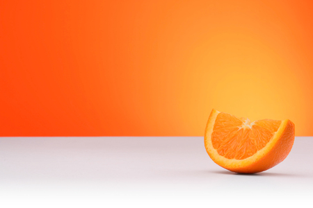 A piece of orange isolated on an orange and white background with space for text