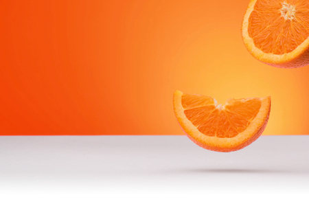 Floating oranges isolated on an orange and white background with space for text 스톡 콘텐츠