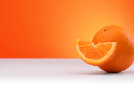 Group of oranges isolated on an orange and white background with space for text
