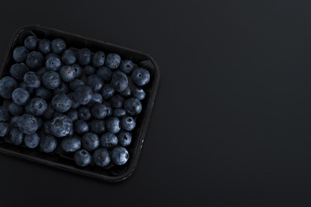 Bunch of blue berries on a tray isolated on black background