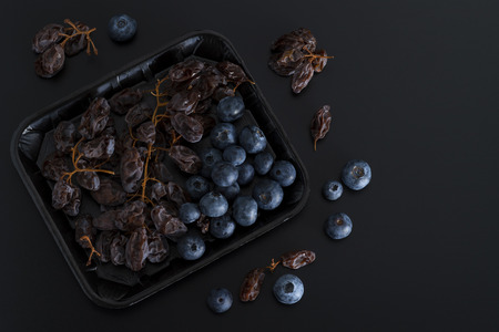 Bunch of dried sultanas and blue berries on a tray isolated on black background