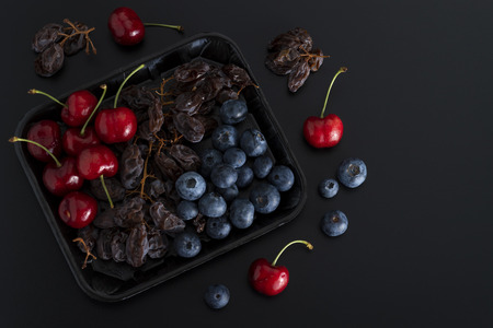 Bunch of dried sultanas, blue berries and cherries on a tray isolated on black background