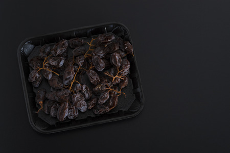 Bunch of dried sultanas on a tray isolated on black background