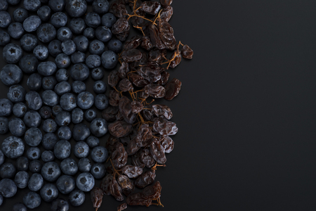 Bunch of blue berries and dried sultanas isolated on black background