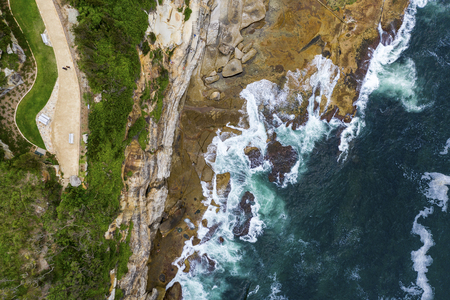 Aerial, overhead view of waves, footpath and a rocky shoreline in Sydney, Australia