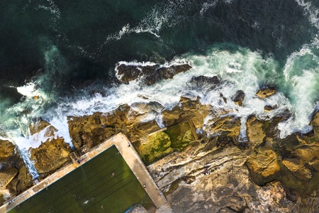 Aerial, overhead view of waves, rock pool and a rocky shoreline in Sydney, Australia