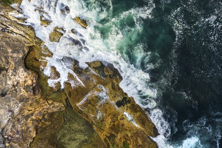 Aerial, overhead view of waves and a rocky shoreline in Sydney, Australia