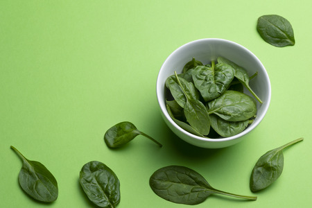 Babe spinach leaves in white porcelain bowl isolated on green background 스톡 콘텐츠