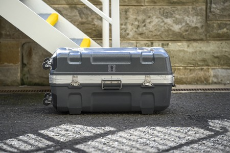 Image of a hard case suitcase laying on the concrete path