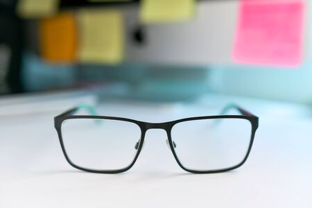 Close up image of black and green eyeglasses on the desk with blur background 스톡 콘텐츠 - 145739874