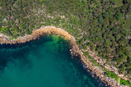 Aerial drone shot of the north coastline of Ku-ring-gai Chase National Park, green tree forest and the rocky coastline with clear turquoise water taken from above, birds eye view landscape