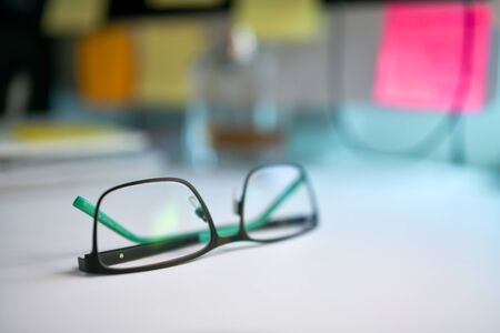 Close up image of black and green eyeglasses on the desk with blur background 스톡 콘텐츠