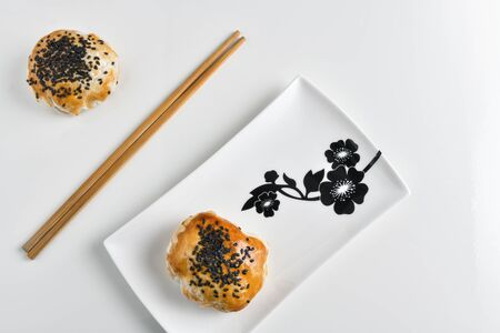 Chinese red bean paste cakes and chopsticks on ceramic plate, isolated on white background