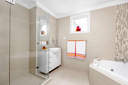 Interior of a modern bathroom with a shower, bathtub and a washbasin.