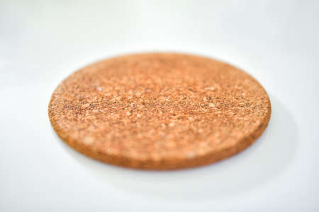 Close up of a cork placemat on white table with blurred background