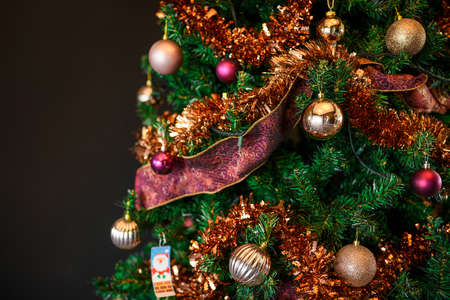 Decorated beautiful Christmas tree on blurred dark background
