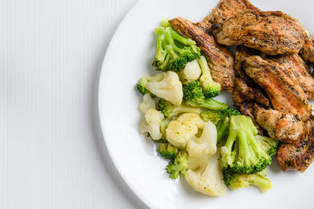 Grilled broccoli, cauliflower and chicken breast on a white plate