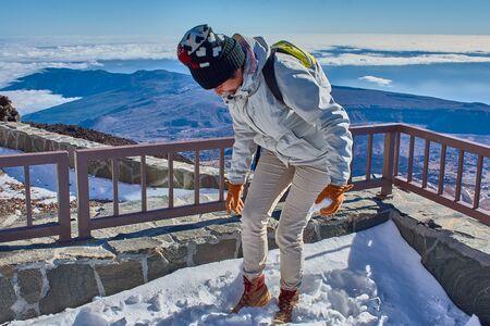 girl having fun playing with snow on the mountain Фото со стока