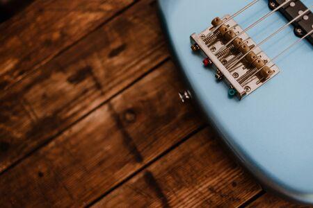 Close up of a blue electric bass bridge on a wooden background Banco de Imagens