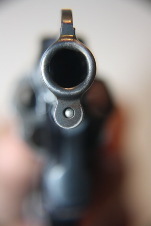 hand holding handgun and pointing it at viewer photo