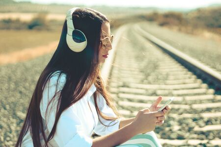 A millennial sitting on train rail track listening music and using mobile phone