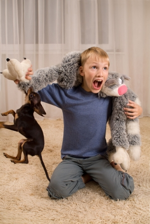 dog toy: Shouting boy playing with a toy and a dog Stock Photo