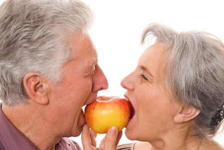woman apple: nice elderly couple eating an apple on a white background Stock Photo