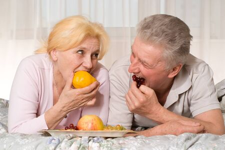 nice old couple lying on the bed and eats fruit photo