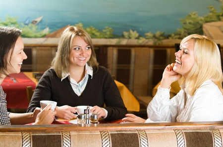 women talking: young women talking at the cafe table