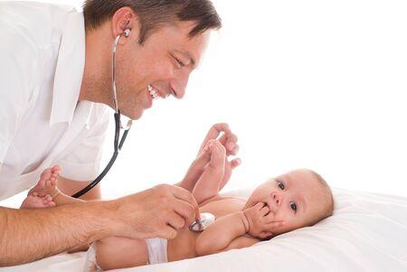 Handsome doctor examining newborn on the white bacground photo