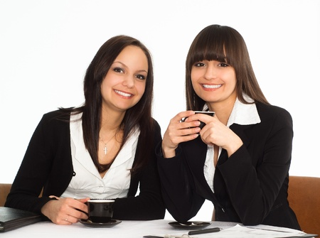 two beautiful business women sitting at the table photo