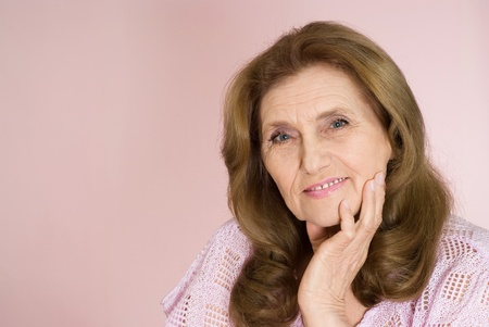 nice elderly woman on a pink background photo