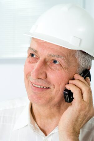 old builder in the helmet on a white background photo