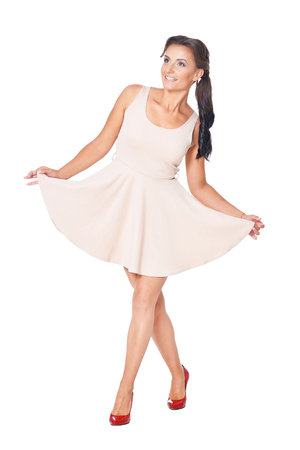 Young beautiful brunette posing in a beige dress on a white background Standard-Bild
