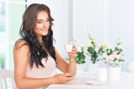 Young beautiful brunette  holds the phone and drinking coffee in the kitchen Standard-Bild