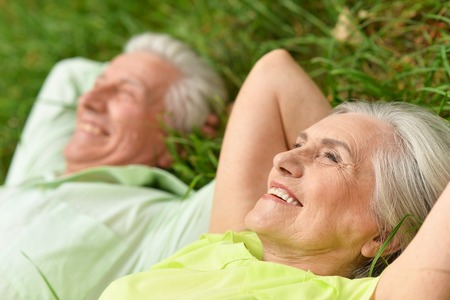 beautiful old people lying on the grass in the park Standard-Bild